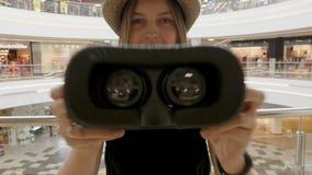 A moça veste um capacete de VR video estoque