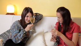 Moças bonitas em um dia chuvoso que senta-se em casa no vinho bebendo, na conversa e no riso do sofá Casa, conforto video estoque