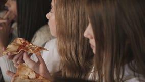 Moças bonitas que comem a pizza e que fuving um divertimento no café 4K video estoque