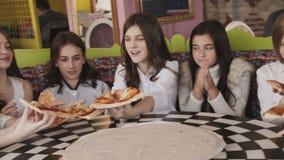 Moças bonitas que comem a pizza e que fuving um divertimento no café 4K vídeos de arquivo