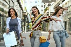 Moças de sorriso que andam na rua com sacos de compras Fotografia de Stock