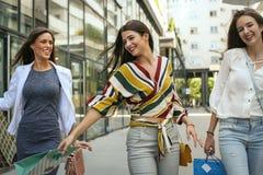 Moças de sorriso que andam na rua com sacos de compras Imagem de Stock