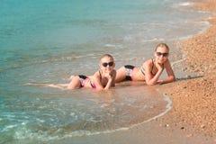 Moças felizes no banho de sol do beira-mar Imagens de Stock Royalty Free
