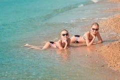 Moças felizes no banho de sol do beira-mar Foto de Stock