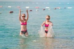 Moças felizes no banho de sol do beira-mar Fotos de Stock Royalty Free