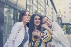 Moças felizes que estão na rua e nas poses junto Fotos de Stock Royalty Free