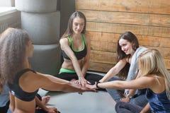 Moças no sportswear no círculo com mãos unidas imagens de stock