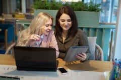 Moças no trabalho atrás do portátil Foto de Stock