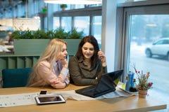 Moças no trabalho atrás do portátil Fotografia de Stock