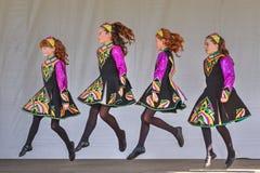 Moças nos trajes coloridos que executam uma dança irlandesa imagem de stock