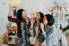 Moças que comemoram o partido de graduação na casa fotos de stock