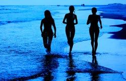 Moças que correm na praia Imagens de Stock Royalty Free