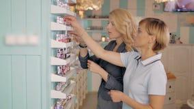 Moças que escolhem o tom novo do verniz para as unhas na loja cosmética, melhores amigos no supermercado Imagem de Stock