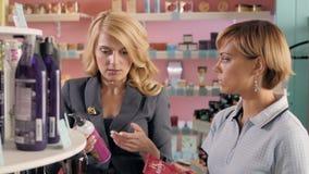 Moças que escolhem o tom novo do verniz para as unhas na loja cosmética, melhores amigos no supermercado Fotografia de Stock Royalty Free