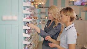 Moças que escolhem o tom novo do verniz para as unhas na loja cosmética, melhores amigos no supermercado Imagens de Stock