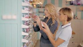 Moças que escolhem o tom novo do verniz para as unhas na loja cosmética, melhores amigos no supermercado Fotos de Stock