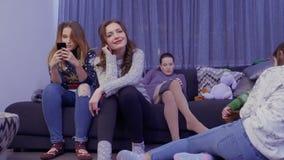 Moças que relaxam em casa e que usam seus telefones vídeos de arquivo