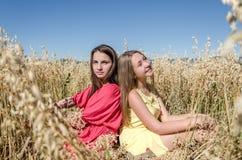 Moças que sentam-se em um campo no sol Fotos de Stock Royalty Free