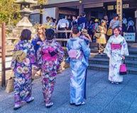 Moças que vestem o quimono japonês que está na frente do templo de Kiyomizu-dera em Kyoto, Japão Fotografia de Stock