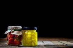 Moździerz, warzywa w słojach dla zimy, drewniany stół w o zdjęcia royalty free