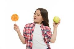 Może robić my szczęśliwi cukrowy słodki smak Dziewczyna trzyma słodkiego lizaka i jabłka Szkolnego lunchu alternatywa Dziewczyna  zdjęcie stock
