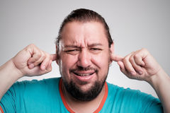 Może słuchać mnie już nie ` t Portret młodzi człowiecy zamyka jego ucho rękami na popielatym zdjęcia stock
