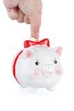 A mão abaixa uma moeda em uma caixa da um-moeda do porco Imagem de Stock Royalty Free