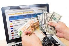 Mão - classificando USD e o EURO na frente da carta da troca de moeda sobre Imagens de Stock