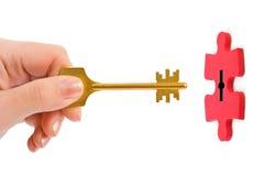 Mão com chave e enigma Imagens de Stock