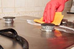 Mão com o fogão de gás de borracha vermelho da limpeza do fulgor Foto de Stock Royalty Free