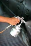 Mão com o injetor da pintura de pulverizador Imagem de Stock