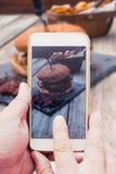 Mão com o telefone esperto, tomando a imagem do alimento do hamburguer Foto de Stock