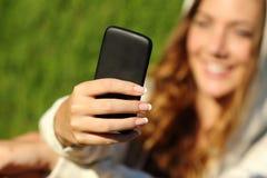 Mão da menina do adolescente usando um telefone esperto com sua cara no fundo Foto de Stock Royalty Free