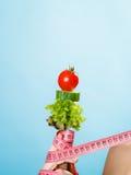Mão da mulher com alimento do vegetariano e as fitas de medição Fotografia de Stock