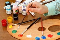 Mão da mulher com pincel, paleta, latas e tubos da pintura Imagens de Stock Royalty Free