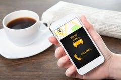 Mão da mulher de negócios que guarda um telefone com o táxi da relação no de Foto de Stock Royalty Free