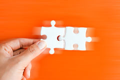 Mão da mulher que cabe a parte direita de enigma que sugere o conceito dos trabalhos em rede do negócio Imagem de Stock