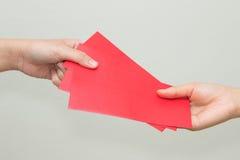 A mão da mulher que dá o vermelho envolve a contenção do dinheiro Fotografia de Stock Royalty Free