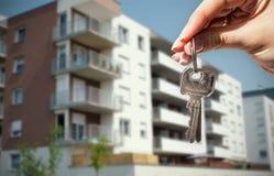 Mão da mulher que guarda chaves com à casa Imagens de Stock