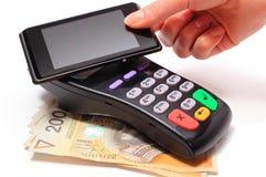 Mão da mulher que paga com tecnologia de NFC no telefone celular Fotografia de Stock