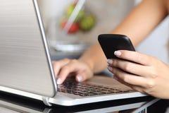 Mão da mulher usando um telefone esperto e datilografando um portátil em casa Imagem de Stock