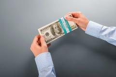 A mão das mulheres que guarda o pacote do dólar Foto de Stock