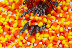 Mão de esqueleto assustador que vem para fora frasco que dá o milho de doces Foto de Stock Royalty Free