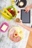A mão de uma mulher com alimento e tabuleta Imagem de Stock Royalty Free