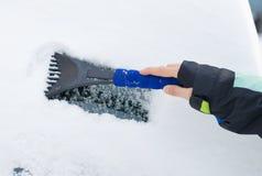 Mão de uma neve de raspagem da mulher e gelo do pára-brisas do carro Imagens de Stock Royalty Free