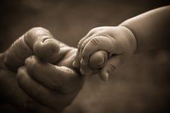 Mão do bebê que guardara o dedo da matriz Imagens de Stock