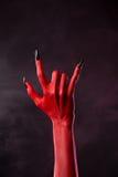 Mão do diabo vermelho que mostra o gesto do metal pesado Fotos de Stock