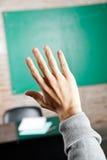 A mão do estudante contra Greenboard na sala de aula Fotos de Stock Royalty Free