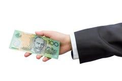 Mão do homem de negócios que guarda os dólares australianos (AUD) em vagabundos isolados Fotografia de Stock