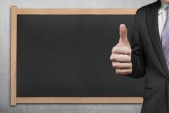 Mão do homem de negócios que mostra o polegar acima com quadro-negro vazio Fotos de Stock